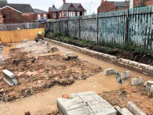 Bricklayer building brickwork up to DPC